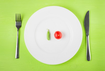 the concept of dietary restrictions, healthy lifestyle, diet,  weight loss, anti-obesity, healthy diet. Small tomato, green peas, on a plate, knife, fork on the table, top view